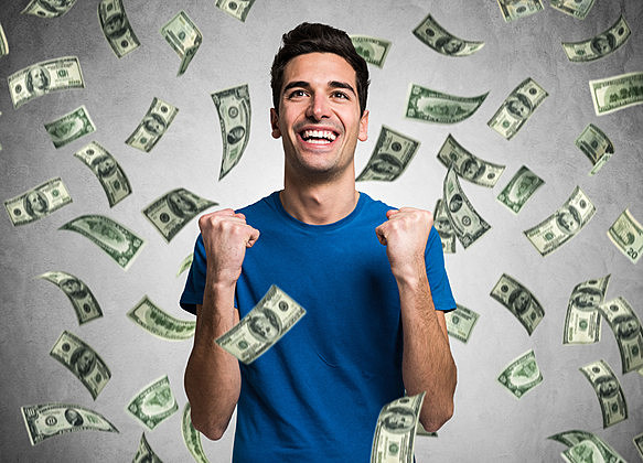 Portrait of a very happy young man in a rain of money