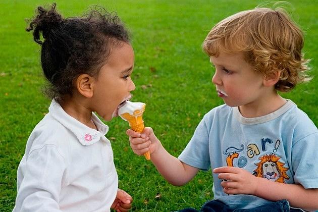 A beautiful mixed race llittle girl sharing a blonde little boy's ice cream